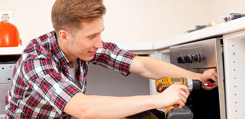 Man-Screwing-Oven-Door-With-Screwdriver