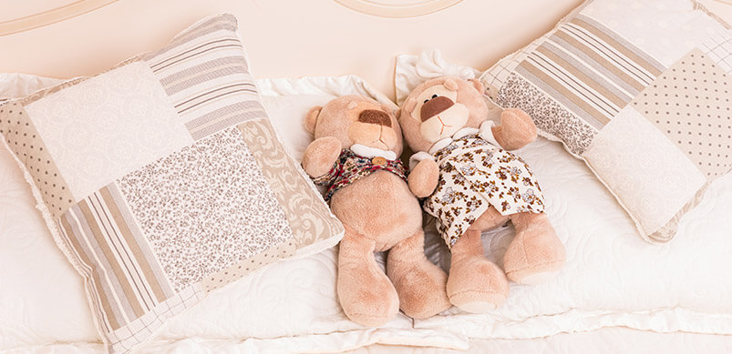 Soft-Toys-And-Cushions-On-Bed